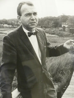 Photo of a man in a bow tie and suit leaning against the railing of a boardwalk