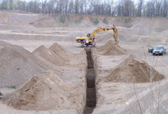 A long trench with dirt piled on both sides and an excavator in the background