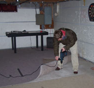 A man drilling a hole in a basement floor