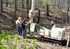 Two workers at a well drilling machine in the woods