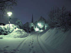 A snow covered path with foot prints in a town at night