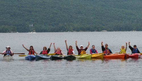 A line of women in kayaks raise their arms in a cheer while floating on a lake