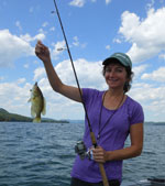 A woman holds up a small fish she caught with a rod.