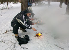 A woman squats to attend to a fire she has started in the snow