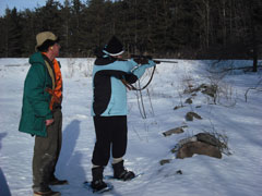 A woman practices shooting a rifle while an instructor observes