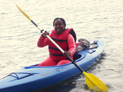 A woman in a red safety vest paddles a blue kayak