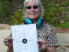 A smiling woman displays her paper target from rifle class