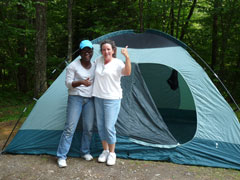Two women give the thumbs up sign while standing in front of the tent they put up.