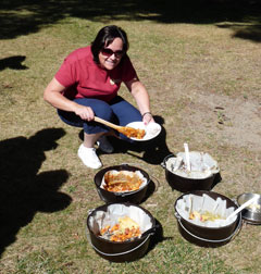 A woman serves herselt from several dishes of fish and game cooking