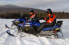 Two environmental conservation officers in red jackets and helmets riding on blue snowmobiles.