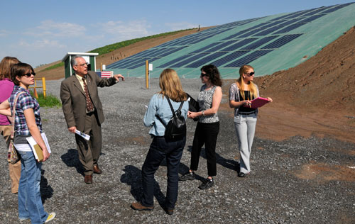 A group of people listen to a man talk in front of a landfill with a solar cap