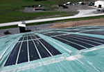 A solar cap with photovoltaic panels covers a portion of a capped landfill