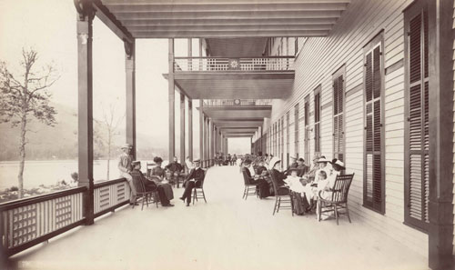 An old photo of a wide covered porch at an inn overlooking a lake