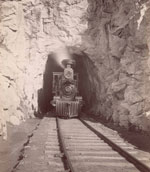 An old photo of a steam train engine emerging from a tunnel in a mountain