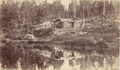 An old photo of a very rustic shack on a wooded slope by a pond.