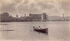 An old photo of a person canoeing on a lake with an Adirondack inn on the shore in the distance