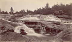 An old photo of small waterfalls and rocky ledges with trees behind