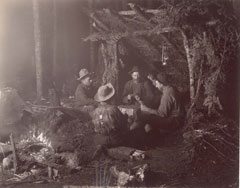 Four men play a card game in front of a rustic leanto in the Adirondacks