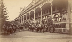 Old photo of horse drawn carriages passing in front of a fancy hotel