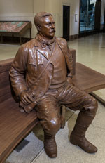A bronze statue of Teddy Roosevelt sitting on a bench inside the museum