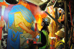 An art conservator with hard hat and headlamp restores a mural on a wall