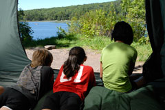 Three campers look out at a lake from inside a tent