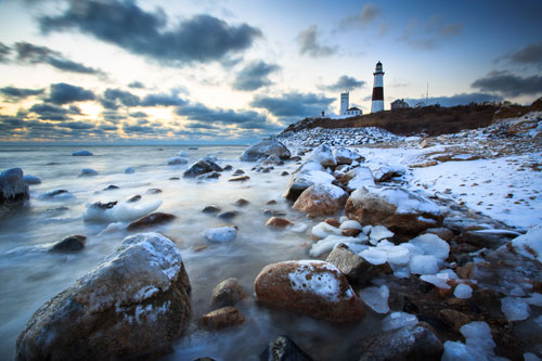 A bouldery coastline and lighthouse in winter with a light coat of snow