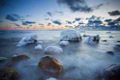 Ice and snow capped boulders in shallow water