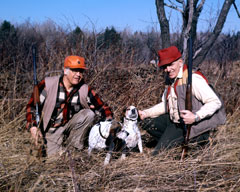 Two rabbit hunters in the field with their dogs