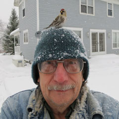 A man outdoors in the snow with a redpoll bird sitting on his hat
