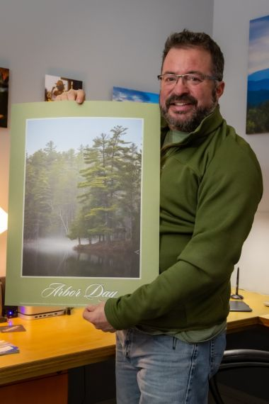Man stands with a poster of his winning photo for the Arbor Day photo contest