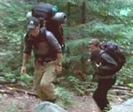 Two well-prepared back country campers hike a forest trail on their way to a secluded, wilderness campsite.