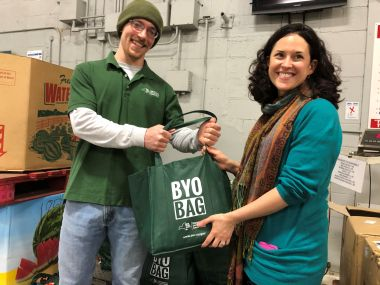 DEC staffer hands off BYOBagNY bag filled with goods to Catherine Shick