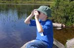 Boy looking through binoculars by the water.