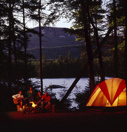 Campers relax around a campfire with the quiet beauty of Lake Durant and the Adirondack mountains in the background.