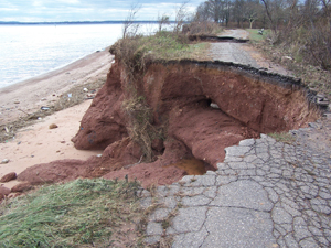 A big gap in the road by the shore of a waterbody that was washed out
