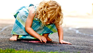 A little blonde-haired, barefoot girl playing on an asphalt driveway