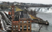 Penstocks behind brown building with Cohoes Falls at the top of the picture