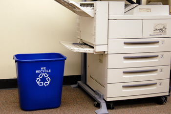 Photocopier with blue we recycle bin and recycle symbol