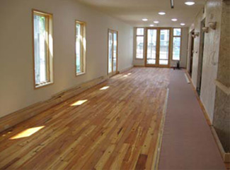 Partially constructed long room with new wood flooring