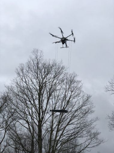 drone hovering in the air carrying equipment