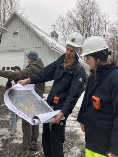 Two DEC staffers look at a map