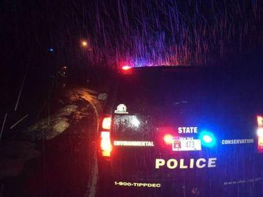 ECO vehicle blocking flooded road on a dark, rainy night with lights flashing