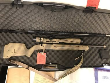 photo of rifle in case with evidence tag on it