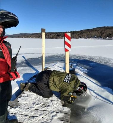 ECO and Forest Ranger on a dock on a frozen lake putting up safety reflectors