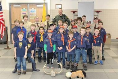 ECO and a large Cub Scout group take a photo in a school cafeteria
