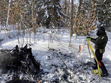ECO putting caution tape up around the burned snowmobile