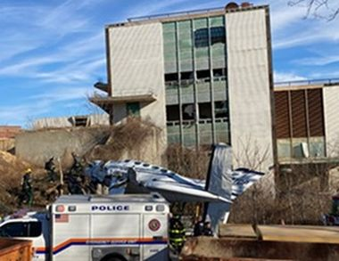 Photo of small plane that has crashed in front of a building