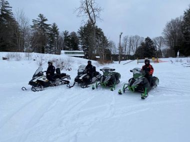 Troopers and ECOs lined up on their snowmobiles for checkpoint detail