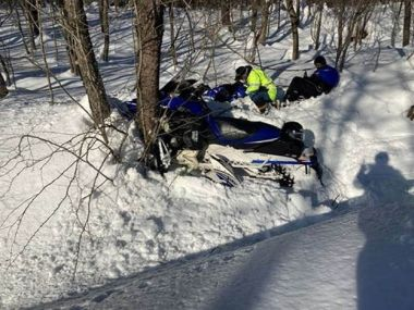 First responder and accident victim at site of snowmobile crash, sitting in the snow next to debris